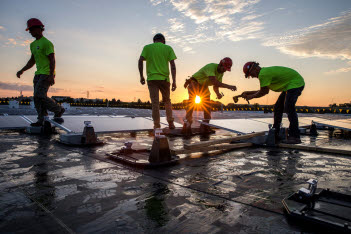 Workers installing solar panels at sunrise