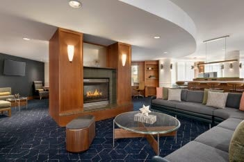 The newly renovated lobby at the Courtyard by Marriott-Lancaster in Greenfield with warm wood tone columns, a glass-top coffee table, sofa-style seating, and navy blue carpeting.